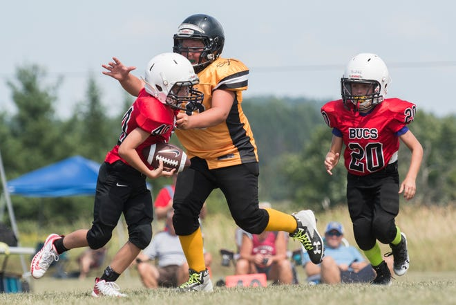 A St. Albans lineman tackles a Chittenden South player during the youth football jamboree on  Aug. 25 in Hinesburg.
