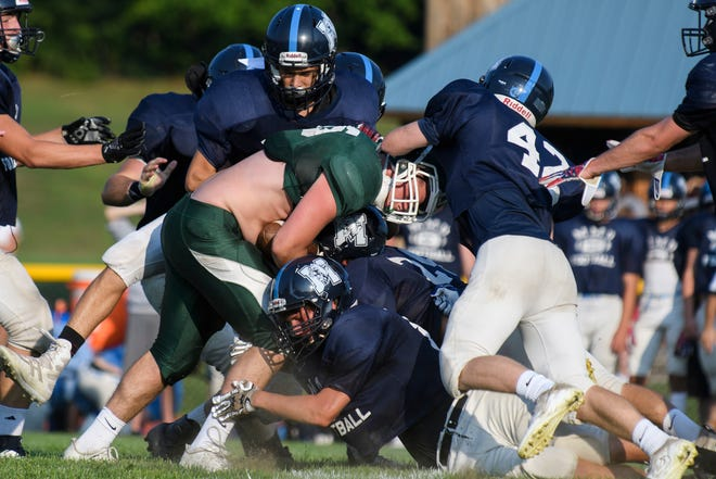 The MMU defense tries to the tackle the St. Johnsbury running back during a high school football scrimmage game between the St. Johnsbury Hilltoppers and the Mount Mansfield Cougars last week in Jericho.
