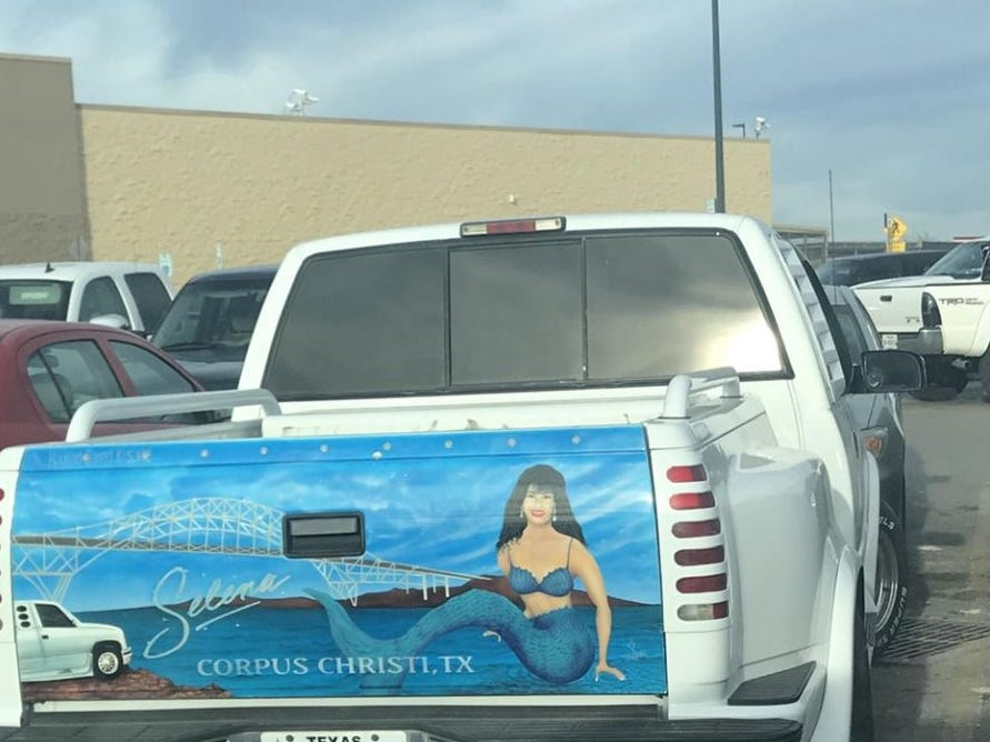 A screenshot shows a white pickup with Selena as a mermaid painted on the tailgate. The painting includes the Harbor Bridge, the white truck and Corpus Christi, Texas.