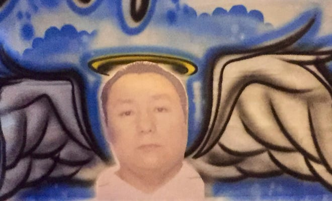 An image of Miguel Rodriguez-Zavala hangs outside the murder victim's restaurant on Federal Street in East Camden.