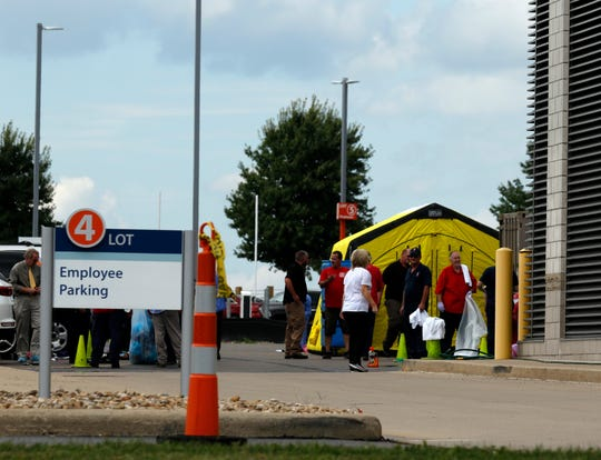 People wait outside a decontamination tent in a parking lot Wednesday, Aug. 29, 2018, at Adena Regional Medical Center in Chillicothe. Earlier in the day the emergency department received 19 patients from the Ross Correctional Institution . Patients and staff in the emergency department were decontaminated.