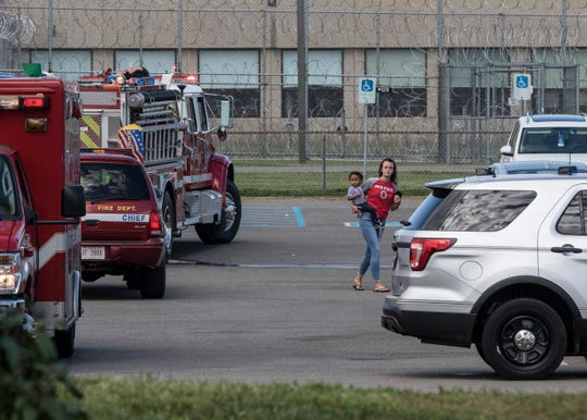 A woman with a small child walks back and forth in the parking lot of the Ross Correctional Institute after trying to talk to emergency officials. The woman, Hannah Riehle, later said she was at the prison for her daughter to see the child's father, who is a RCI inmate.
