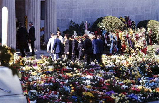In this Aug 18, 1977 file photo, pallbearers carry the flower-covered coffin of Elvis Presley into the Forest Hills Cemeteries mausoleum in Memphis, Tenn. After a thief tried to snatch his body, the remains of both Elvis and his mother were moved to a garden at Graceland.
