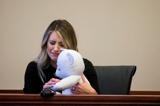 Katie Carter, Ryan Poston's sister, holds a teddy bear made out of one of Ryan's shirt and presses a button to play Ryan's voicemail message during the sentencing hearing of Shayna Hubers, 27, who was found guilty of murdering Ryan Poston, at the Campbell County Courthouse Wednesday, August 29, 2018 in Newport, Kentucky. Carter said that this is all her family has left of Ryan.