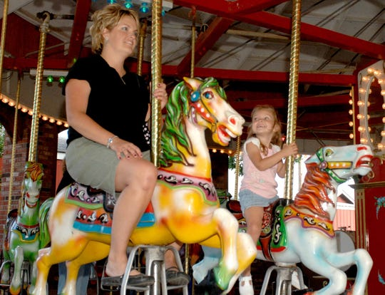 Tammi Hesselbrock of Brookville, Indiana and daughter Emilee Hesselbrock, age 3, ride the Merry-go-round  at Stricker's Grove Amusement Park in Ross, Ohio in 2008.