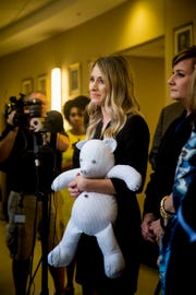 Katie Carter, Ryan Poston's sister, holds a teddy bear made out of Ryan's shirt and answers questions from the media after Shayna Hubers was given a life sentence for the murder of Ryan Poston at the Campbell County Courthouse Wednesday, August 29, 2018 in Newport, Kentucky.