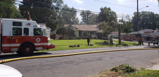 A firefighter grabs a bottle of water while at a house fire on Sherman Avenue in Plainfield.