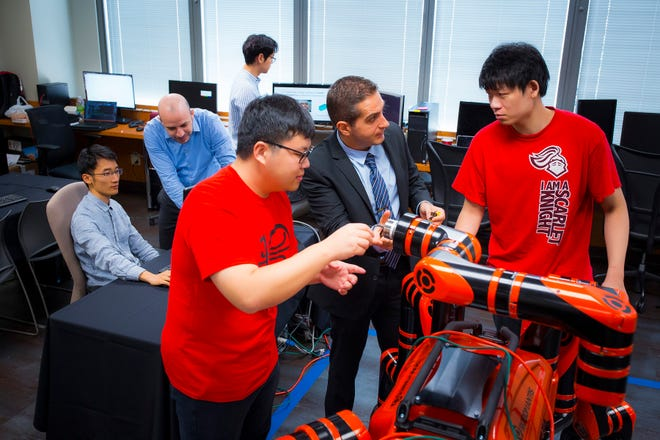 Rutgers Professor of Computer Science Kostas Bekris demonstrates the RoboMantis robot's abilities with School of Arts and Sciences senior Zetao Yu, left, majoring in mathematics and computer science, and Shuai Han, right, graduate student in computer science, in the new Rutgers robotics lab in downtown New Brunswick.