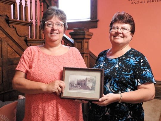 Vickie Davis and Jacque Wagner with a photo of the Rose of Sharon Retreat being built in the late 1890s by original owner Thomas Powelson.