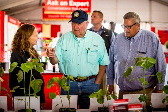 U.S. Secretary of Agriculture Sonny Perdue, center, and Under Secretary for Farm Production and Conservation Bill Northey, right, ask questions of Meaghan Anderson in the Iowa State University pavilion during a tour of the Farm Progress Show on Aug. 29 near Boone.