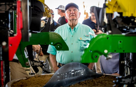 U.S. Secretary of Agriculture Sonny Perdue looks at a planting unit made by Precision Planting during a tour of the Farm Progress Show Aug. 29, 2018, near Boone, Iowa.