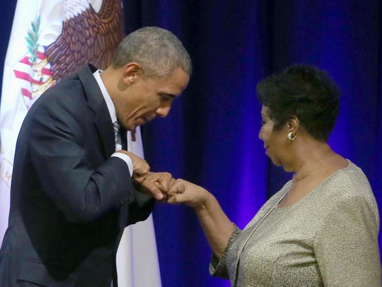 President Barack Obama fist bumps with Aretha Franklin, who sang during a farewell ceremony for Attorney General Eric Holder at the Justice Department on Feb. 27, 2015, in Washington, D.C.