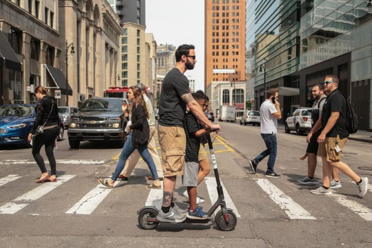 Adrienne Belford of Philadelphia (not seen) follows along as her boyfriend Costantino Spinosa of Philadelphia rides with her son Jack Glenn on a rented Bird electric scooter near Campus Martius in downtown Detroit on Monday, August 20, 2018 while ending their trip to Detroit. The group tried multiple scooters that were out of power before finding the one they used.