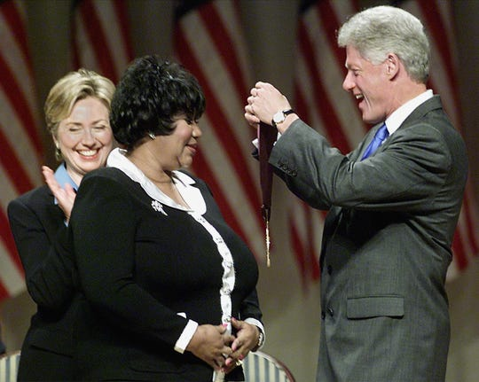 FILE -- President Bill Clinton along with First Lady Hillary Rodham Clinton award singer Aretha Franklin with the 1999 National Medal of Arts and Humanities Award in September 1999 in Washington, DC.