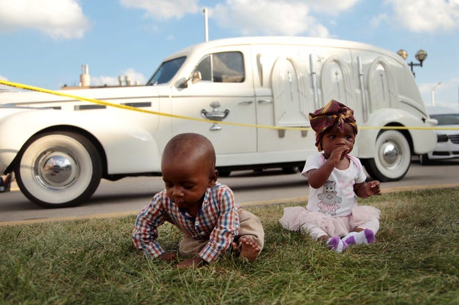 Aliyah Afriye Miyzaan, right, and Ali Miyzaan, both of Ann Arbor, sit beside Swanson Funeral's 1940 LaSalle hearse,  that carried the late Aretha Franklin to the Charles H. Wright Museum of African American History, for a public viewing in Detroit on Tuesday, August 28, 2018.