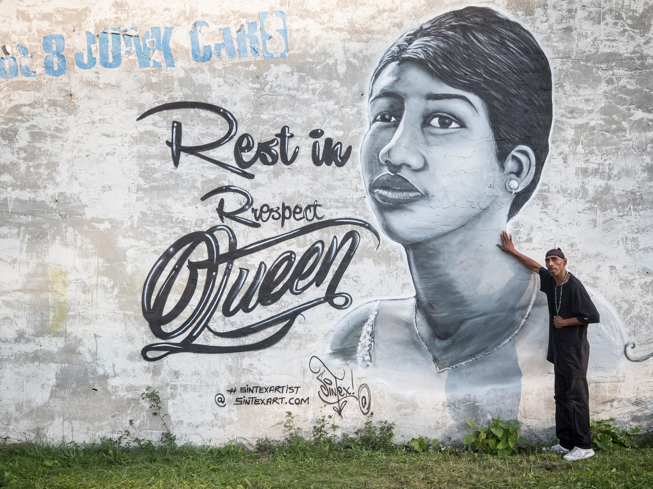 Kenneth Burns of Detroit poses for a photo in front of a mural painted by artist Sintex honoring Aretha Franklin near Linwood Street and Euclid Street in Detroit, Tuesday, August 21, 2018.