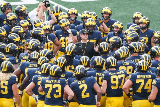 Michigan head coach Jim Harbaugh, right, talks to players during an open practice at the Michigan Stadium in Ann Arbor, Sunday, August 26, 2018.