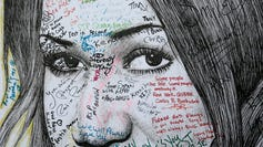 People write farewell messages on a drawing of Aretha Franklin by artist Mark Gaines, of Harlem, on the second day of a public viewing for Franklin at the Charles H. Wright Museum of African American History in Detroit on Wednesday, Aug. 29, 2018.
