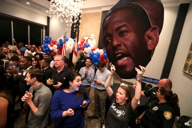 Rachelle Clegg holds an Andrew Gillum cutout as she cheers on gubernatorial candidate Andrew Gillum at his watch party at Hotel Duval in downtown Tallahassee, Fla., Tuesday, Aug. 28, 2018.