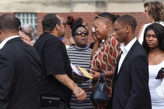 Family members of Detroit firefighter Jack C. Wiley II wipe tears before the memorial service at St. John's Church in Detroit on Wednesday.
