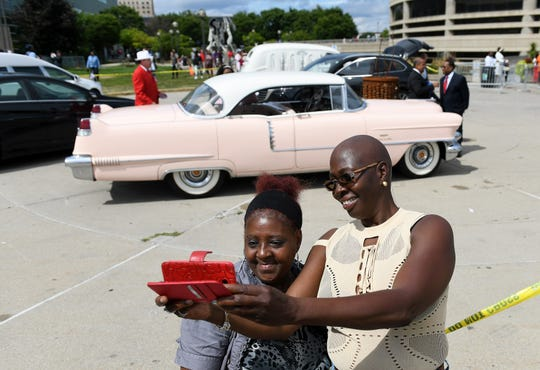 Theresa Isrow, right, takes a photo with her friend, Renee Davis, both of Detroit in front of a pink 1957 Cadillac DeVille outside the Charles H. Wright Museum of African American History where Aretha Franklin lays in state for the public in Detroit on Aug. 29, 2018.