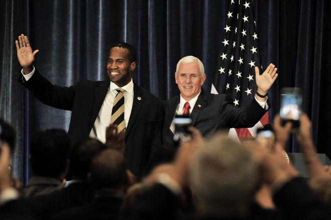 Republican U.S. Senate candidate John James, left, waves to the crowd after introducing Vice President Mike Pence Wednesday at a campaign stop in West Bloomfield.