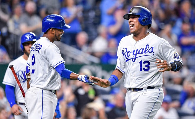 The Kansas City Royals' Salvador Perez (13) is greeted by Alcides Escobar after Perez scored on a two-run double by Hunter Dozier in the third inning.