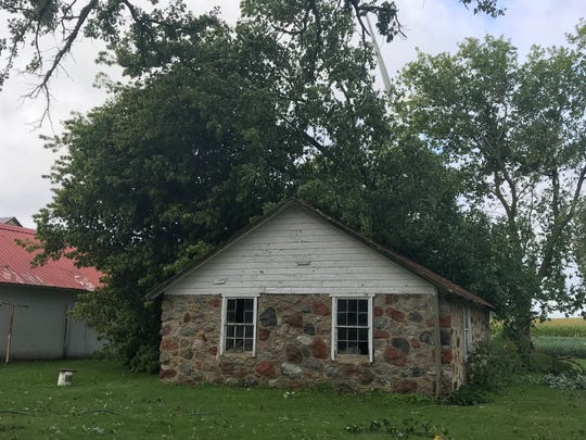 A tree planted by Glenn Kalkhoff's grandsons 35 years ago fell on an old stone building in his backyard.