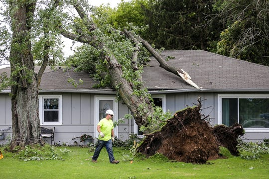 Tony Voigt of K&B Tree and Lawn Care makes his way around a tree on a house Wednesday at N3041 South Frontage Road near Waupun. Severe weather Tuesday afternoon raked across the Waupun area causing widespread damage.