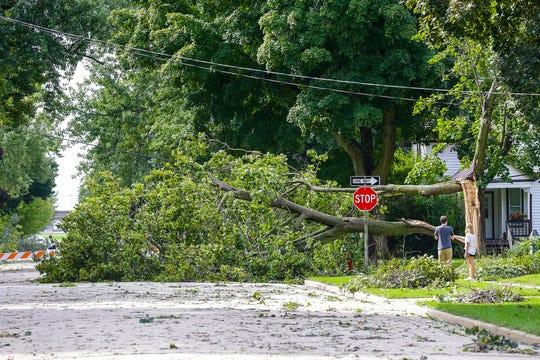 Isaac Lont and Heaven McGinnis of Waupun look at a downed tree Wednesday at the intersection of Hillyer and Brown Streets in Waupun. Severe weather Tuesday afternoon raked across the Waupun area causing widespread damage.