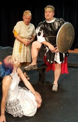 """Tia Wightman (Geminae) smiles at Kevin Held (Miles Gloriosus) as Jimy Forman (Pseudolus) looks on during a dress rehearsal of """"A Funny Thing Happened on the Way to the Forum."""""""