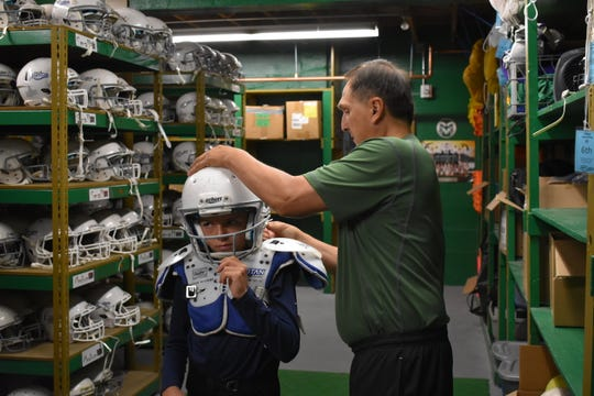 Jorge Perez helps sixth-grader Billy Greenwood find a proper-fitting helmet during equipment checkout for the city of Fort Collins' youth tackle football program.