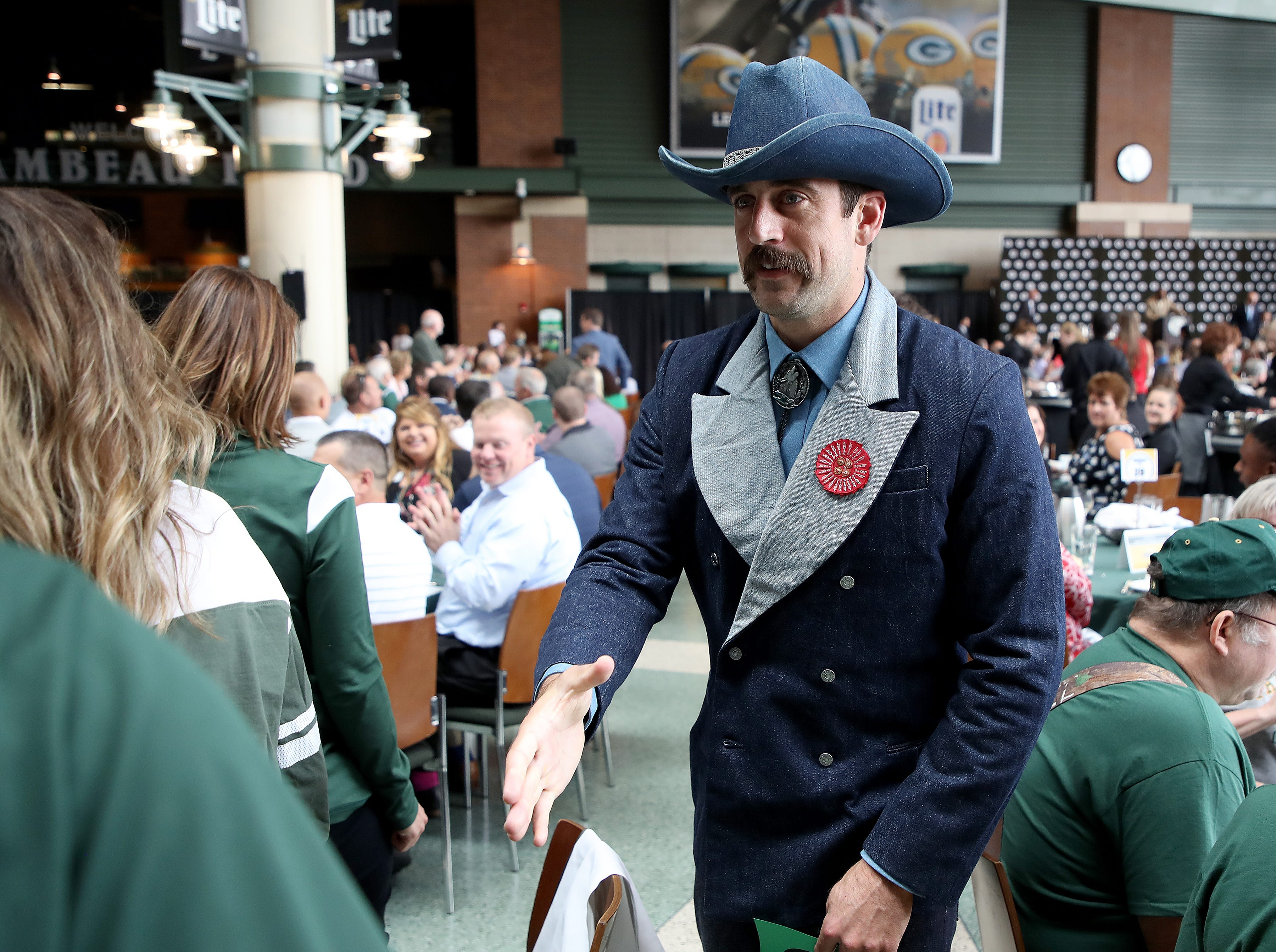 Green Bay Packers quarterback Aaron Rodgers (12) greets people at his table during the Green Bay Chamber of Commerce Welcome Back Packers Luncheon at Lambeau Field Wednesday, August 29, 2018 in Green Bay, Wis.