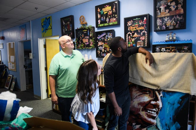 Will Ragland, Manny Houston and Carly Stelling look at old photographs from their youth performing at the South Carolina Children's Theatre on Tuesday, Aug. 28, 2018.