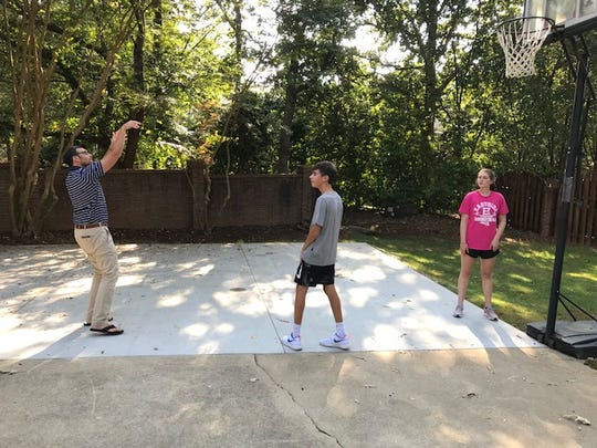 Paul Jimenez, left, joins his children Harrison and Emma Grace for some basketball. The Jimenez parents say banning TV on weekdays has helped their children stay healthy and given them more family time.