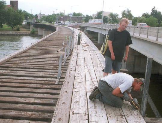 Doug Wicks, assisted by Ron Siefke, removes railings in 1999 from the old Milwaukee Road bridge for refitting work.