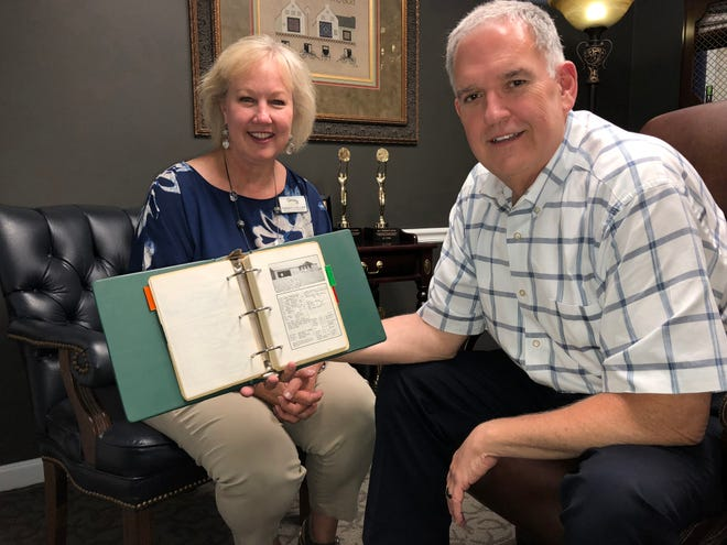 Jim and Christy Collier display an old three-ring binder that shows printed Multi Listings from an earlier era. Today, such listings are found online and in smartphone apps.