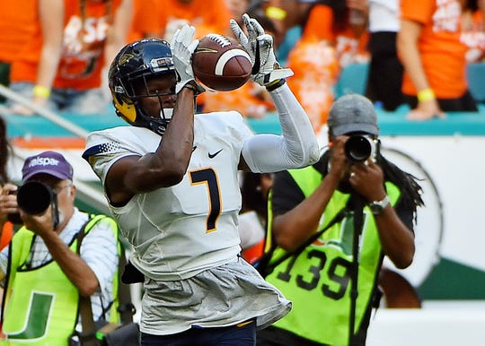Toledo Rockets wide receiver Jon'Vea Johnson (7) makes a catch before running for a touchdown against the Miami Hurricanes during the first half at Hard Rock Stadium.