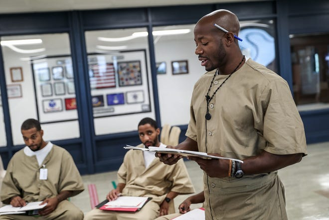 "Chris Lewis reads a written piece out loud to fellow inmates during a writing class at the Plainfield Correctional Facility in Plainfield, Ind., Wednesday, Aug. 15, 2018. The Indiana Prison Writers Workshop teaches creative writing skills to inmates through reading and writing prompts. The workshop inspired Lewis to write a book, ""Dear Solomon: Love is the Why,"" based on a fellow inmate's real-life story. Since becoming incarcerated, Lewis begun singing and playing guitar and says the class has helped his lyric writing."