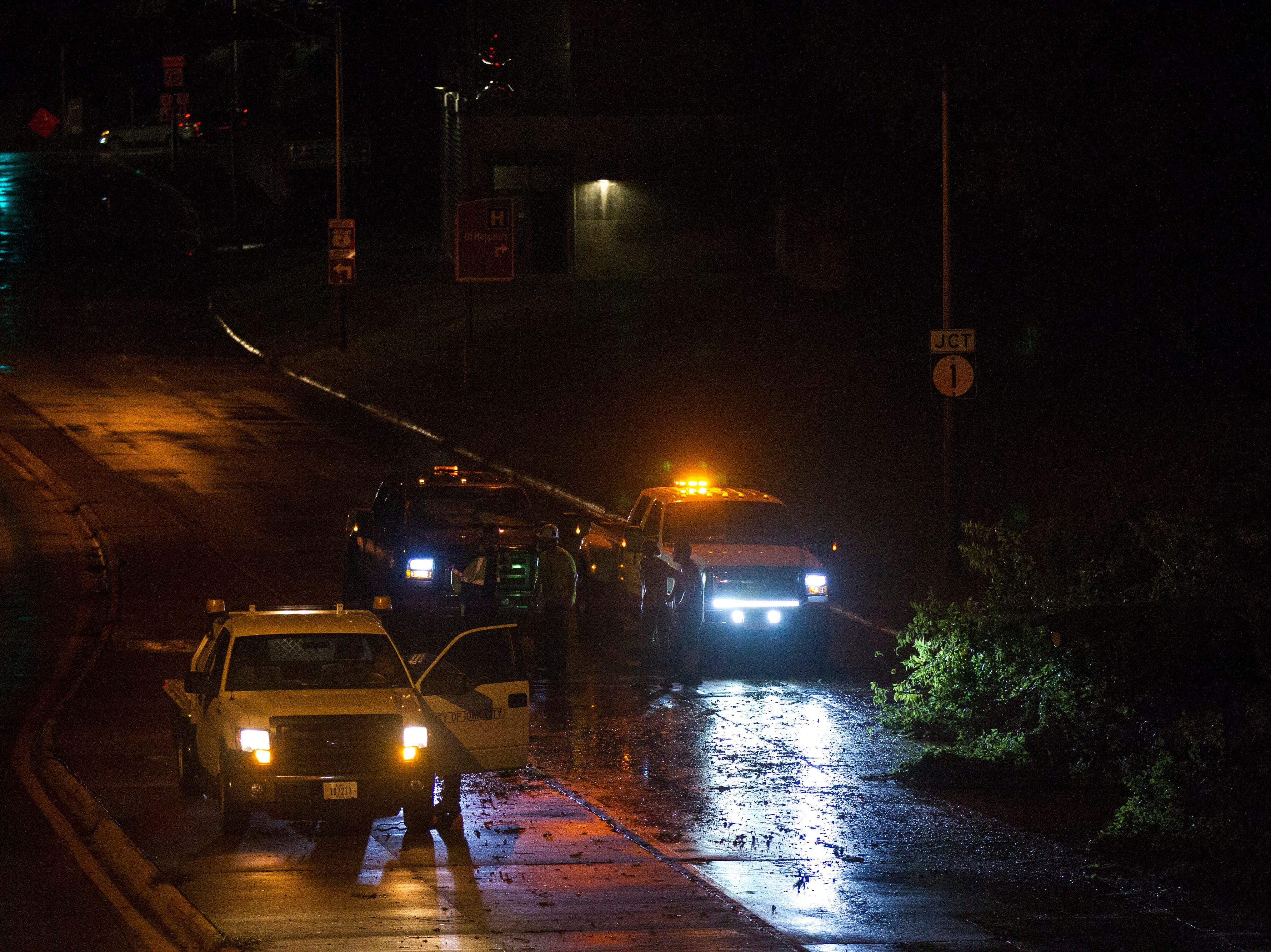 Responders move a tree out of the road during a rain storm on Tuesday, Aug. 28, 2018, on Riverside Drive in Iowa City.