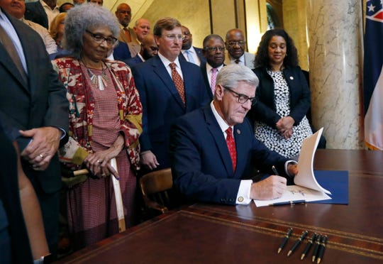 Republican Gov. Phil Bryant, seated, reaches for a pen to sign the Mississippi Infrastructure Modernization Act, before legislation supporters at the conclusion of the Special Session of the Legislature, Wednesday, Aug. 29, 2018, at the Capitol in Jackson, Miss. The act designed to help solve the state's crumbling infrastructure of roads and bridges, passed earlier in the week. Lawmakers hailed the bipartisan support in its passage. (AP Photo/Rogelio V. Solis)