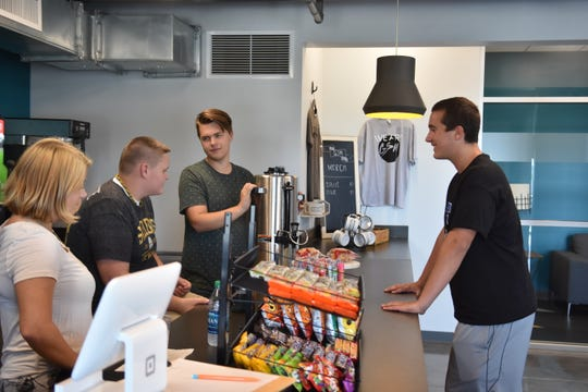 Justin West, far right, chats with workers in the cafe at Grace Student MInistry.