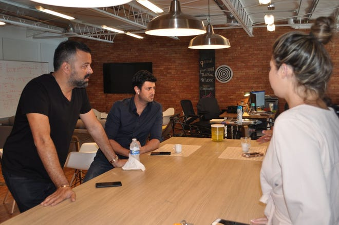 Ozan Baran (left), Founder and CEO of BOS Group Inc., a multi-million dollar logistics company in Miami, speaks with two of his employees at Quickload LLC -- account manager Engin Sekucoglu (center) and administrative assistant Nicolle Zabian (right). (Marianna Schiavino)