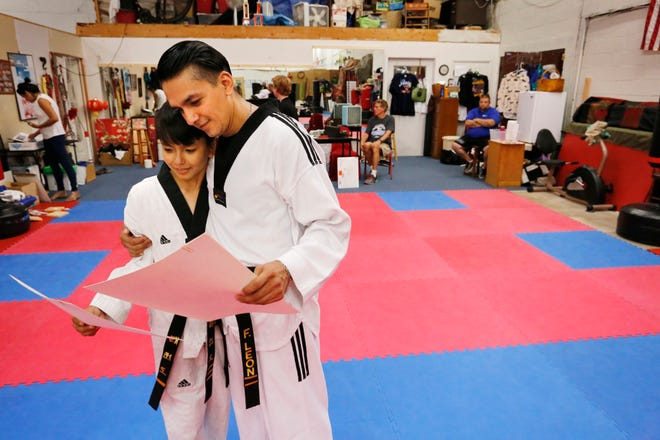 Felipe Leon embraces his son, Brandon, after they were both awarded their Dan certificates after passing the respective tests in Taekwondo at American House of Martial Arts Tuesday, August 28, 2018, inside Trader Buck's Flea Market, 2330 Sagamore Parkway South in Lafayette. Felipe Leon, 37, received is third Dan, or third degree black belt, in Taekwondao. Brandon received his one Dan, or first degree black belt.