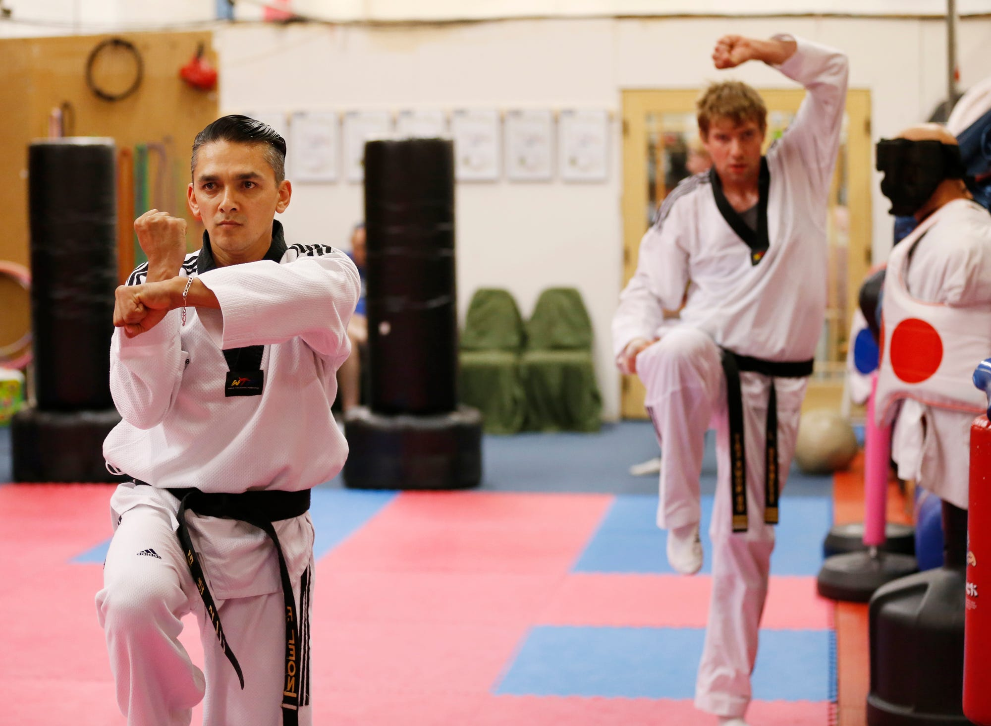Felipe Leon, foreground, and Lucas Bennett demonstrate forms as they test for black belts in Taekwondo at American House of Martial Arts Tuesday, August 28, 2018, inside Trader Buck's Flea Market, 2330 Sagamore Parkway South in Lafayette. Forms are fighting techniques used as if fighting an opponent. Each form has a specific set of movements. Leon, 37, received his three Dan, or third degree, black belt. Bennett, 27, received his for Dan, or fourth degree black belt.