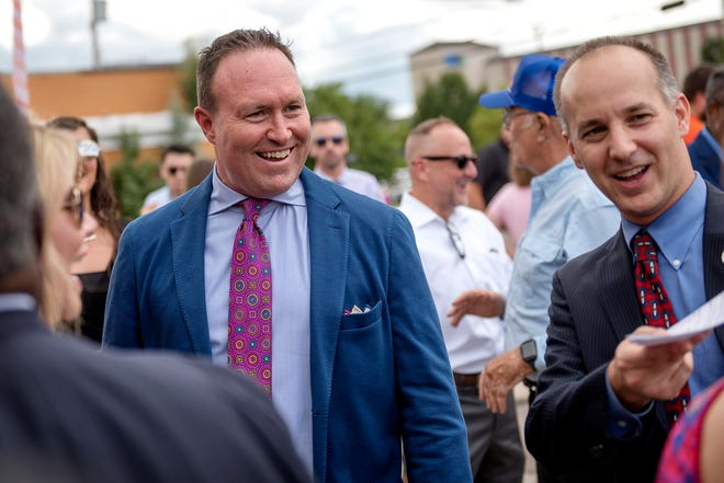 Pat Gillespie, of the Gillespie Group, left, mingles with the crowd including Mayor Andy Schor, right, during an event announcing the planned development of a grocery store and hotel at the 600 block of East Michigan Avenue on Wednesday, Aug. 29, 2018, in downtown Lansing. The project is part of a mixed-use developmentÊslated to open by theÊend of 2020.