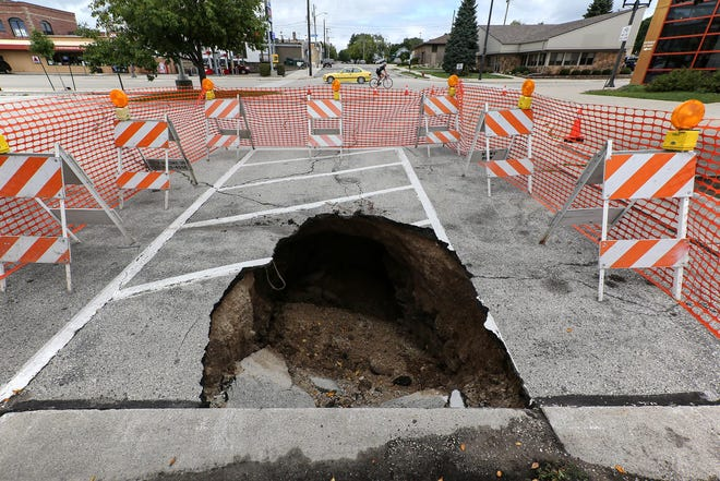 A sinkhole caused by yesterday's heavy storms is blocked off in the Wisconsin Maritime Museum parking lot Wednesday, Aug. 29, in Manitowoc.