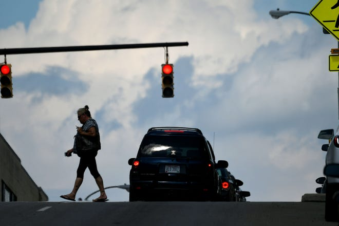 A pedestrian crosses Diamond Street at the crosswalk with a background of clouds Wednesday afternoon during a walk downtown.