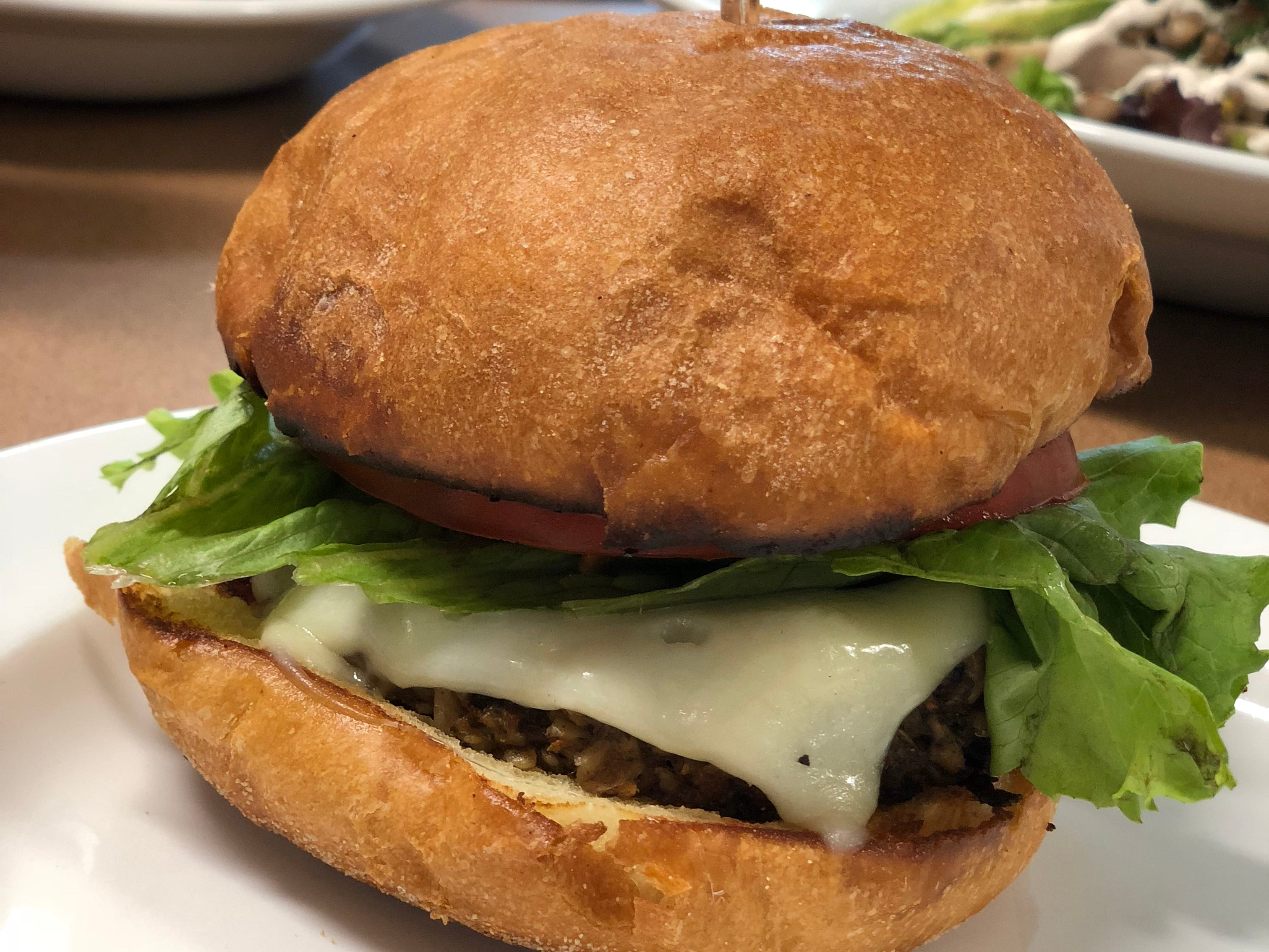 The newly re-opened Caritas Village cafe is serving veggie burgers from Fuel.  They are also serving traditional burgers with grass fed beef from Marmilu Farms.
