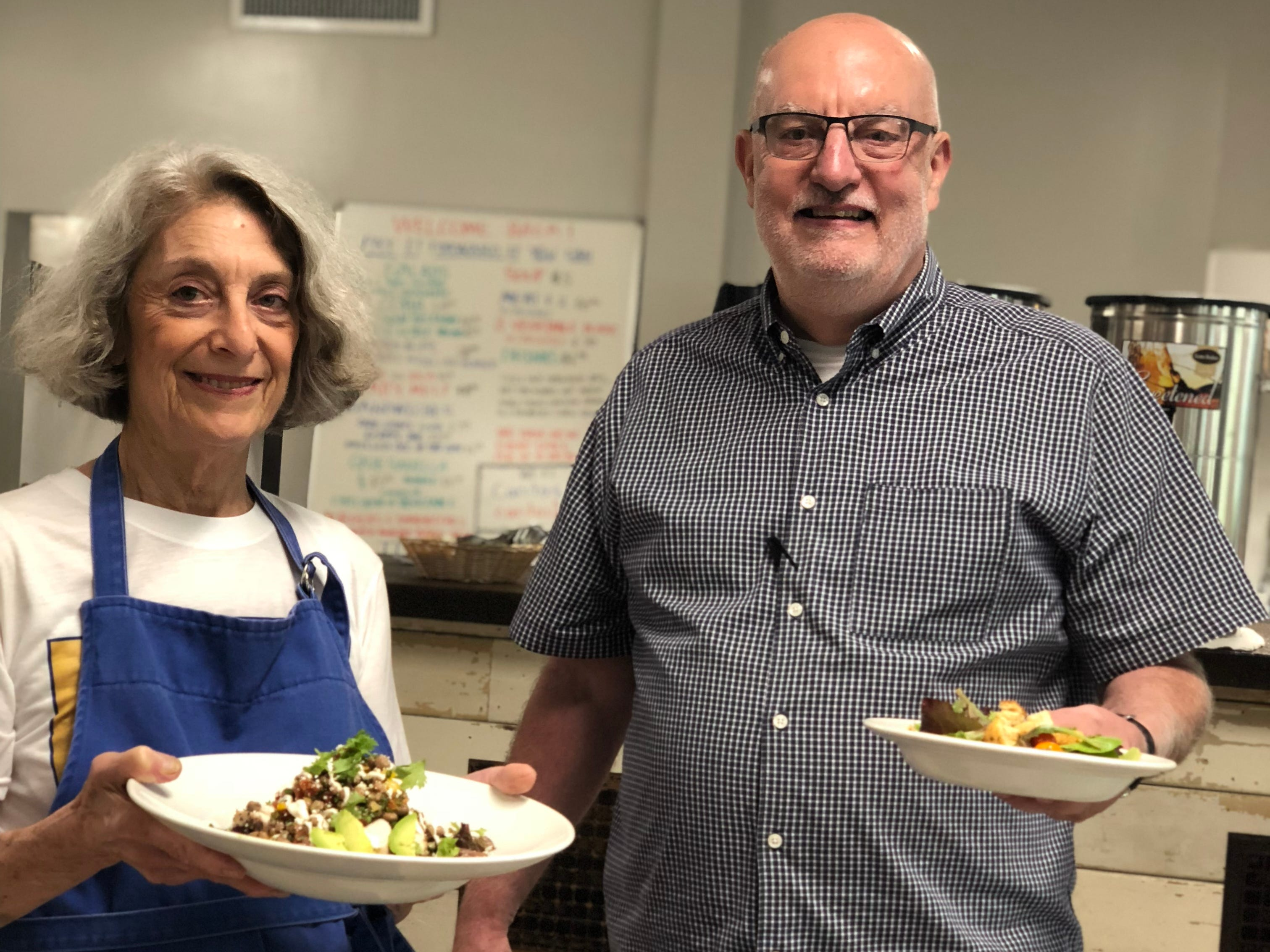 Caritas Village Executive Director Mac Edwards, right, and longtime volunteer Eddie Thomas, left, serve lunch with a smile on the cafe's re-opening day.